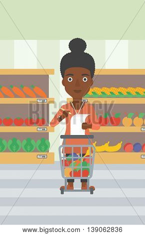 An african-american thoughtful woman standing at the supermarket with supermarket trolley full with products and holding a shopping list in hands. Vector flat design illustration. Vertical layout.