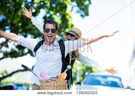Cheerful couple with arms outstretched on bicycle in city
