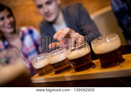 Close-up of man taking beer glass at restaurant
