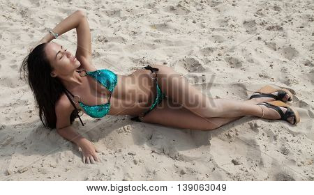 attractive sexy asian woman in bikini, outdoor shot in sand, summer day. Beauty at the beach sand around. Fashion shot of beautiful woman on the beach.