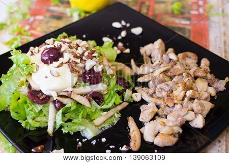 Italian salad with cherry, roasted chicken and Chinese cabbage on the black plate
