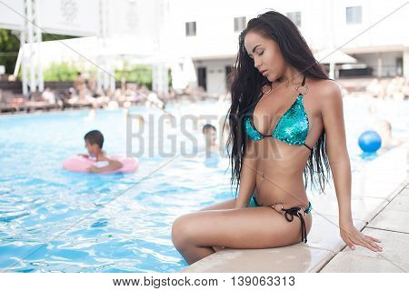 Beautiful brunette girl in good shape with long dark hair and tan skin red lips in fashion swimming suite hat lie seating near the pool beach smile summer hot tan party. Sexy buttocks.