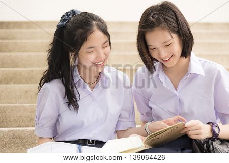Cute Asian Thai high schoolgirls student couple in school uniform sit on the stairway discussing homework or exam with a happy smiling face. The cover of the brown book is Thai text means