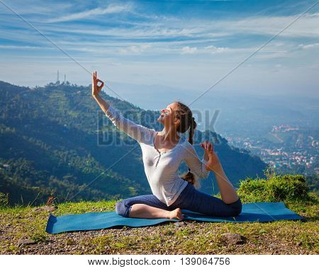 Yoga outdoors - young sporty fit woman doing stretching yoga asana Eka pada rajakapotasana - one-legged king pigeon pose in Himalayas mountains, India