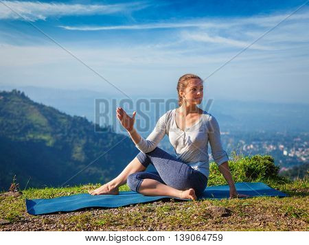 Yoga exercise outdoors -  woman doing Ardha matsyendrasanaasana asana - half spinal twist pose mountains in Himalayas in India in the morning