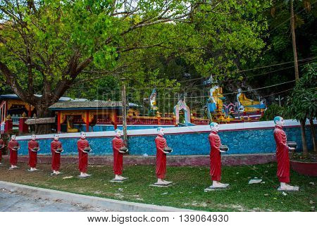 Many Sculptures Of Monks At The Entrance To The Sacred Cave That Face Each Other. Hpa-an, Myanmar. B