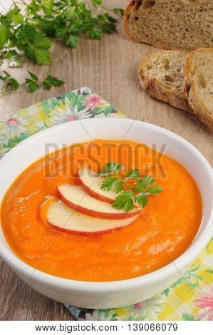Plate of sweet pumpkin puree soup with apple