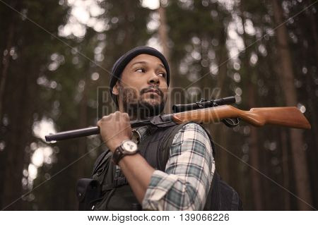 Interracial hunter in the forest with rifle