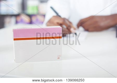Black pharmacist or doctor writing with tablet package with copy space