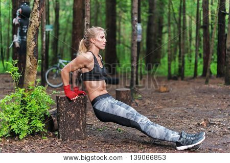 Fit woman doing triceps dips at park. Fitness girl exercising outdoors with own bodyweight.