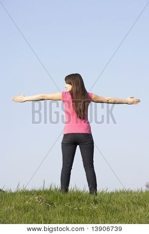 Teenage Girl Standing In Summer Meadow