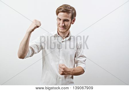 Joyful, Very Happy Smiling Young Adult Male in White Shirt Pumping His Fists