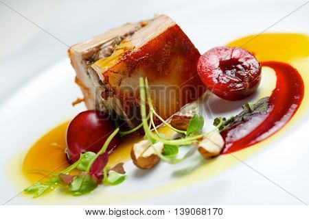 Piglet with cherries in a white plate.