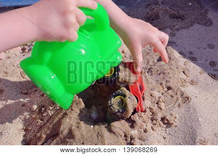 Children's hands playing in the sand with toys