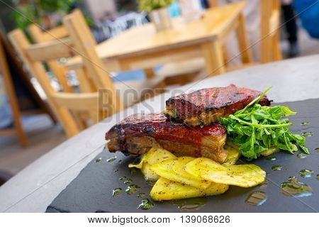 Closeup of a rib with potatoes and vegetables.