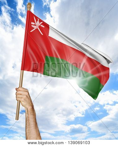 Person's hand holding the Oman national flag and waving it in the sky, 3D rendering