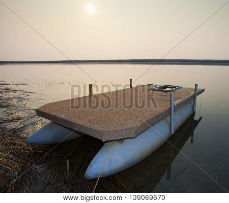 Sun rising over a beached pontoon boat on a lake in Canada