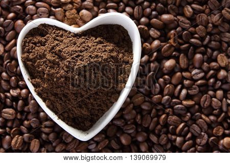 coffee podwer in a heart shape container on top of coffee beans