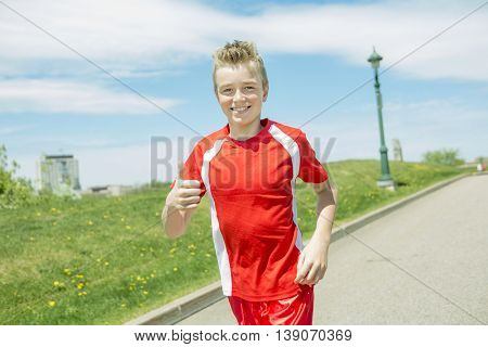 A teen boy run outside in a day light
