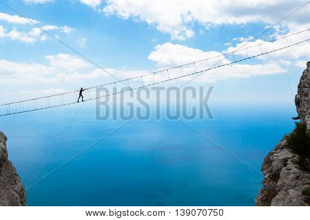 Man climbing on the suspension bridge to the peak of mountain.