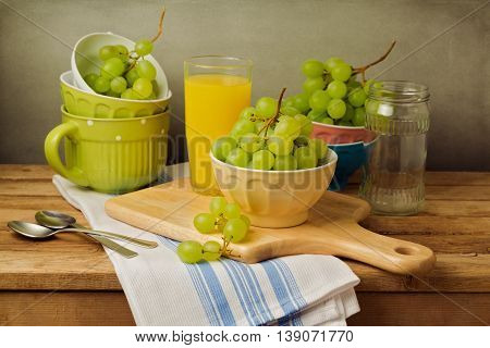 Still life with grapes on wooden table over grunge background