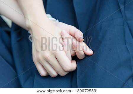 Asian Thai high schoolgirls students couple holding hands with love and friendship with blue school uniform skirt