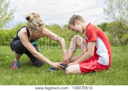 An Athletic boy Holding her Painful ankle