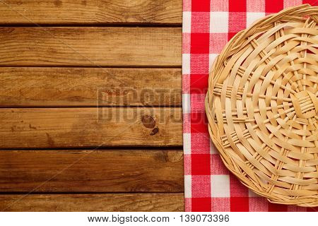 Background with wooden deck board checked tablecloth and wicker plate