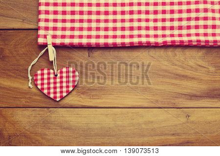 Retro toned background with checked tablecloth and heart shape on wooden board