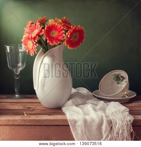 Still life with orange gerbera flowers on wooden table