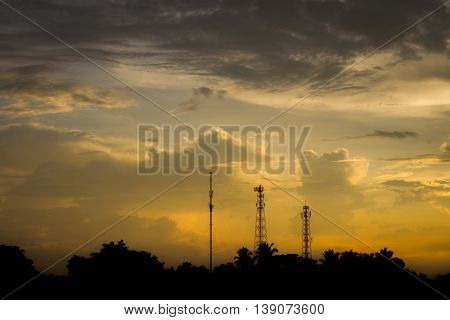Silhouette communication antennas in evening cloudy sky.