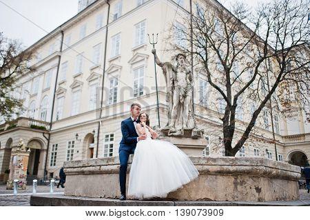 Wedding couple siting near Poseidon monument at wedding day