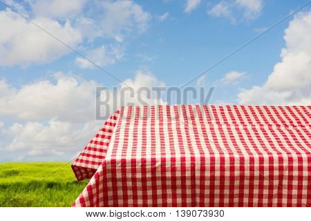 Empty table covered with red checked tablecloth over beautiful sky. Ready for product montage