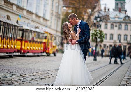 Wedding couple walking on tram ways at wedding day