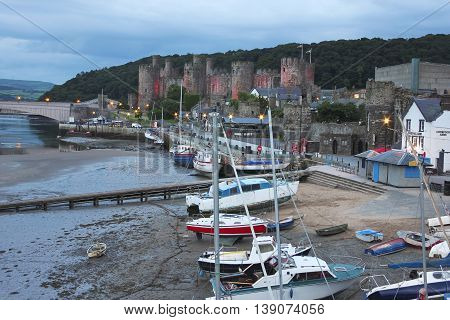 CONWY, WALES, JUNE 27. Conwy Castle on June 27, 2016, in Conwy, Wales. Boats moored at low tide along Lower Gate Street near Conwy Castle in Conwy Wales.