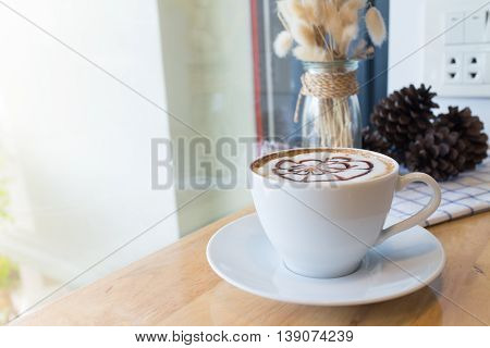 hot coffee with foam milk art. Hot coffee in afternoon break. Coffee mocha on the wood desk. Coffee break.(selective focus vintage effect)