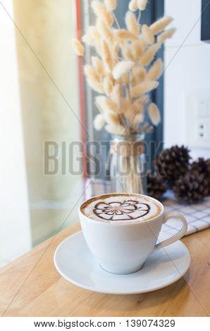 hot coffee with foam milk art. Hot coffee in afternoon break. Coffee cup. coffee mocha on the wood desk. Coffee break.(selective focus vintage effect)