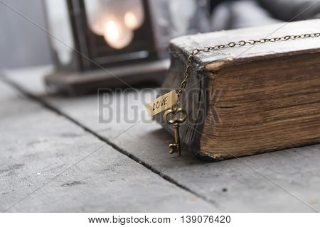 Religion idea, the Bible and the key with the word love on the table and Vintage Lantern.