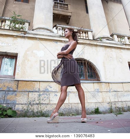 Beautiful girl walking near the old mansion with columns in summertime