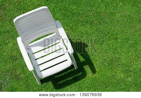 Top view of a empty garden chair on law.