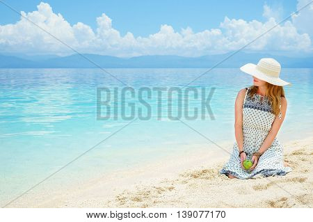 young european woman in dress, hat and with green apple is sitting on the sand beach of calm tropical sea ay sunny day under blue sky