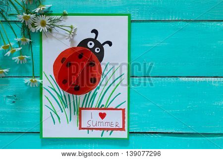 Colorful Paper Card With Ladybug, Grass, And The Words I Love Summer, Camomile On A Blue Wooden Back