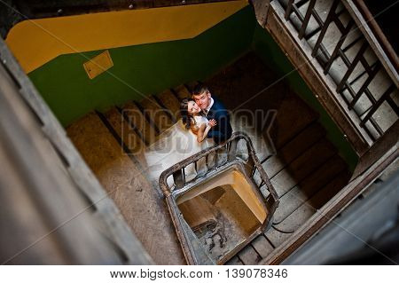 Wedding Couple At Wooden Stairs In The Entrance Of An Old House