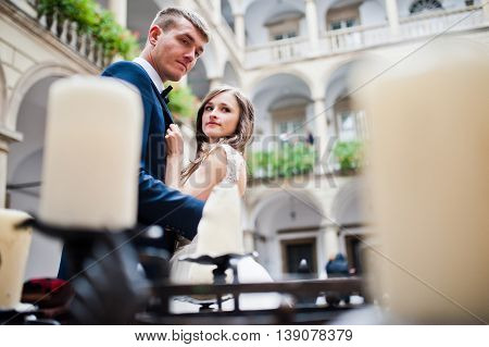 Wedding Couple Near The Old Candlesticks With Candles