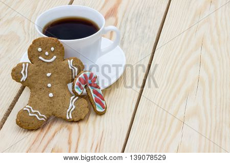 Homemade gingerbread cookie man and cup of coffee on wooden table
