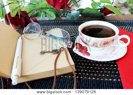 Cup with coffee, old notebook with brown leather cord and key, glasses,pen .roses, red doily in on the dark blue bamboo napkin.