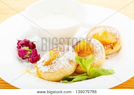 Cheesecakes on a white plate with sour cream, jam decorated with mint and roses