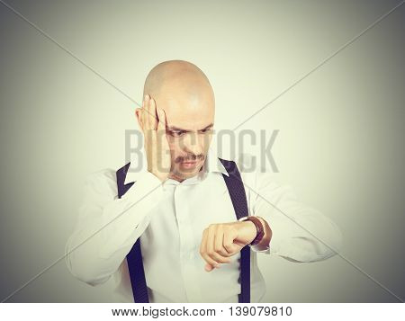 Bald Businessman Looks At His Watch