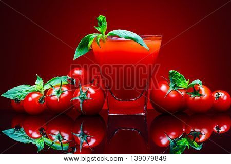 Beautiful red tomatoes, a glass of tomato juice on red background with reflection and Basil ilstyami