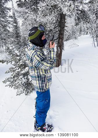 A snowboarder with a in the winter forest in cloudy day